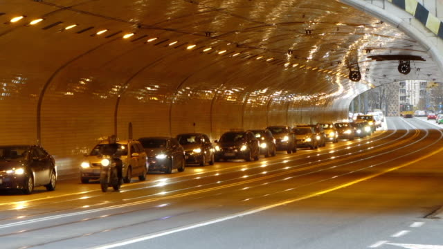 Automobiles driving with caution into tunnel equipped with new lights, traffic