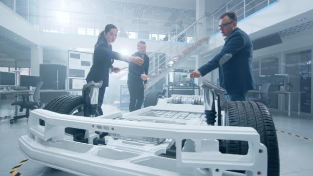 automotive design engineers talking während der arbeit am elektroauto chassis prototyp. in der innovation laboratory facility concept vehicle frame beinhaltet räder, hängepartie, motor und batterie. - design stock-videos und b-roll-filmmaterial