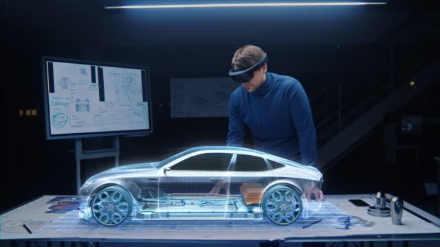 автомобильный инженер ношение vr гарнитура работает над 3d электрический автомобиль дизайн, используя жесты в дополненной реальности он про - моторное транспортное средство стоковые видео и кадры b-roll