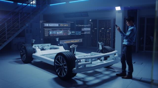 Automobilingenieur arbeitet auf Elektroauto Chassis Plattform, mit Tablet-Computer mit Augmented Reality 3D-Software. Innovative Einrichtung: Fahrzeugrahmen mit Rädern wird zu einem soliden virtuellen Modell. – Video