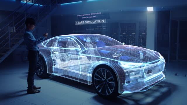 Automobilingenieur arbeitet auf Elektroauto Chassis Plattform, mit Tablet-Computer mit Augmented Reality 3D-Software. Innovative Einrichtung: Fahrzeug-Virtual-Mesh-Modell wird auf Aerodynamik getestet. – Video