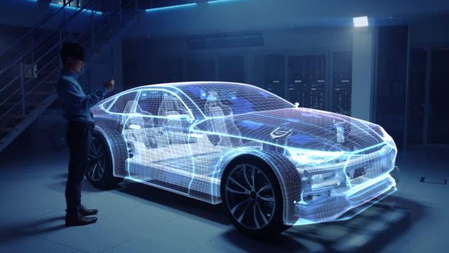 автомобильный инженер, работающий на платформе шасси электромобиля, используя планшетный компьютер с 3d-программным обеспечением дополнен - моторное транспортное средство стоковые видео и кадры b-roll