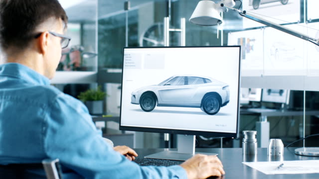 automotive engineer works on the personal computer, he perfects new car model prototype sketch. he works in the bright and modern office. - моторное транспортное средство стоковые видео и кадры b-roll