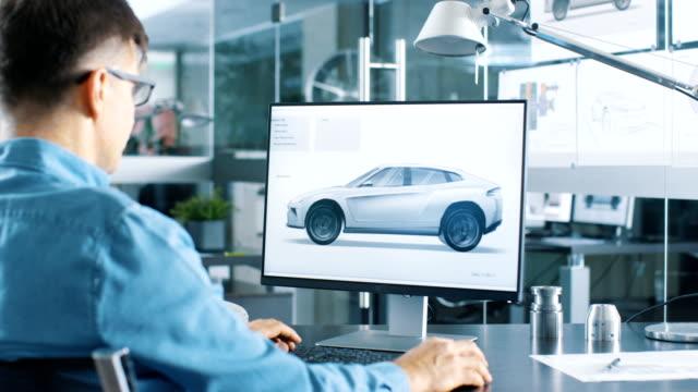 автомобильный инженер работает на персоном компьютере, он совершенствует новый прототип модели автомобиля эскиз. работает в ярком и совре� - моторное транспортное средство стоковые видео и кадры b-roll