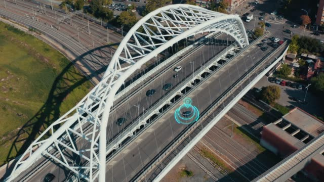 Autonomous Self Driving Car Concept. Aerial view of Electric car moving on city bridge with Artificial Intelligence scans road with sensors and GPS tracking. Future Transportation concept video