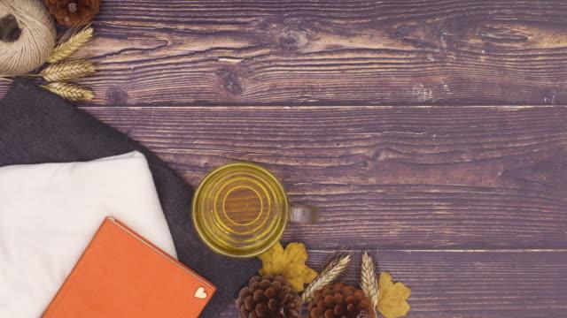 vidéos et rushes de composition d'automne avec livre, tasse de thé et détails d'automne. stop motion - boisson chaude