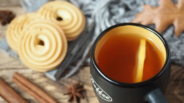 autumn concept cozy home. a slice of lemon floats in a cup of tea. cookies on a wooden table - bevanda calda video stock e b–roll