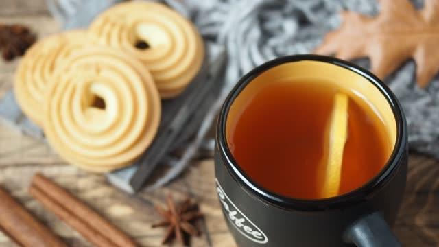 vidéos et rushes de maison confortable de concept d'automne. une tranche de citron flotte dans une tasse de thé. biscuits sur une table en bois - boisson chaude