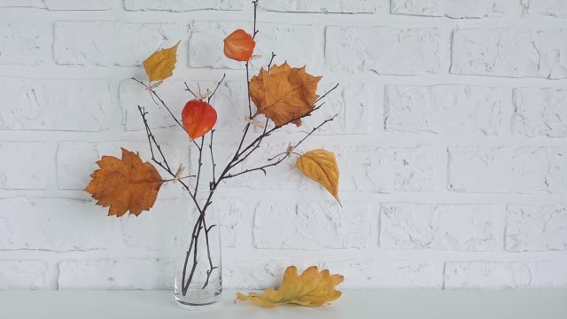 Autumn creative bouquet of branches with yellow leaves on clothespins in vase on table background white brick wall Copy space Minimal style. Template for postcard, text, design Concept Hello autumn