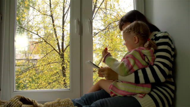 Autumn day, mother and daughter playing on the windowsill in the tablet. video