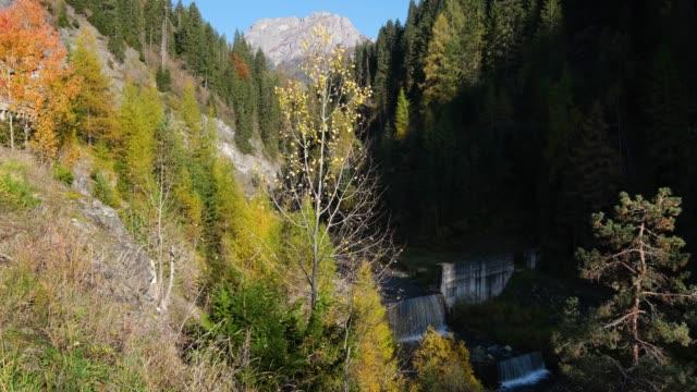Autumn Dolomites scene with waterfall cascades on mountain river, Sudtirol, Italy
