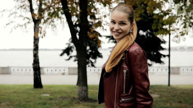 stockvideo's en b-roll-footage met herfst is in aantocht. gelukkige vrouw in bordeaux lederen jas lopen in de straat, tikje stad - paardenstaart haar naar achteren