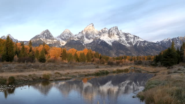 autumn morning clip of the teton mountains reflected in calm water