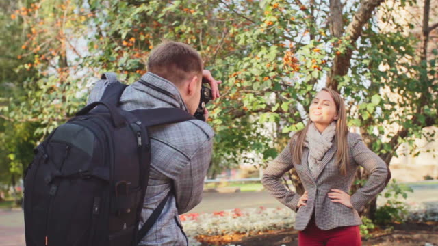 Autumn Photo Shoot Man taking picture of his girlfriend posing in front of tree and smiling arms akimbo stock videos & royalty-free footage