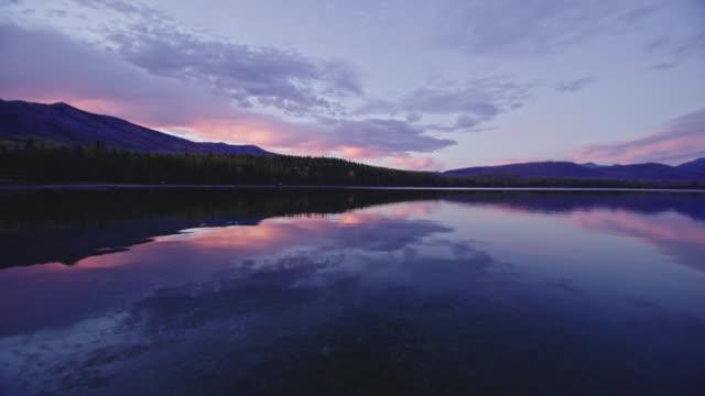 Autumn scene looking across lake at colorful sunset at Lake McDonald in Montana