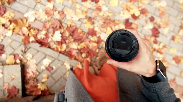 vídeos y material grabado en eventos de stock de otoño. vista superior de joven elegante con relojes inteligentes tomando café. hojas de arce hermoso caído fullhd - moda de otoño