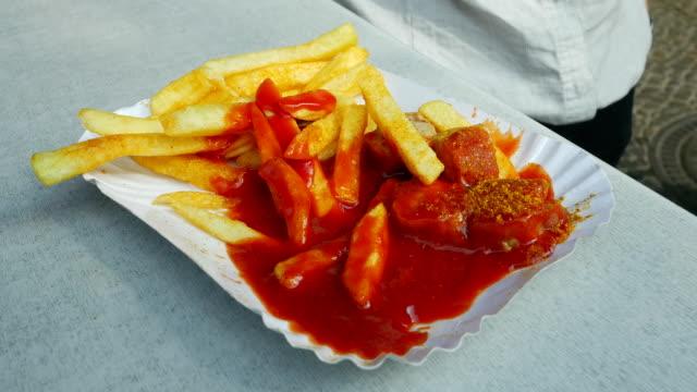 durchschnittliche frau isst currywurst und pommes frites (4 k uhd zu/hd) - wurst stock-videos und b-roll-filmmaterial