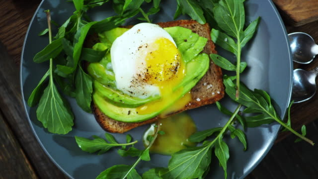 Avocado and egg sandwich Avocado and egg sandwich served with arugula. Close-up crane shot avocado stock videos & royalty-free footage