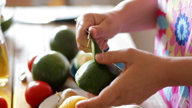 vídeos de stock e filmes b-roll de avocado fruit peeling, close-up, steadicam - abacate