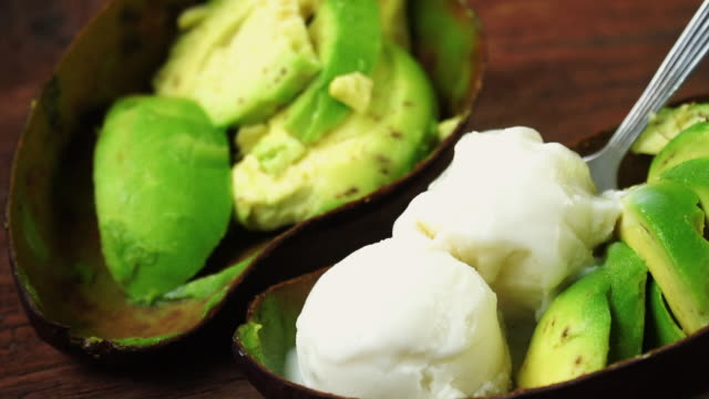 Avocado Ice cream, Made with Organic fresh avocados and milk on wooden table. Healthy fruits concept. Selective focus and free space for text. Avocado Ice cream, Made with Organic fresh avocados and milk on wooden table. Healthy fruits concept. Selective focus and free space for text. avocado stock videos & royalty-free footage