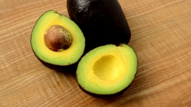 vídeos de stock e filmes b-roll de avocado on a wooden board. - abacate