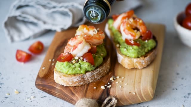 Avocado Shrimp Toast With Olive Oil Pouring Olive Oil On Avocado Shrimp Toast In Slow Motion. Healthy Food avocado stock videos & royalty-free footage