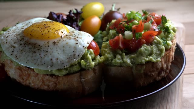avocado toast topped with diced tomatoes chopped green onion drizzled with olive oil and fried egg - avocado video stock e b–roll