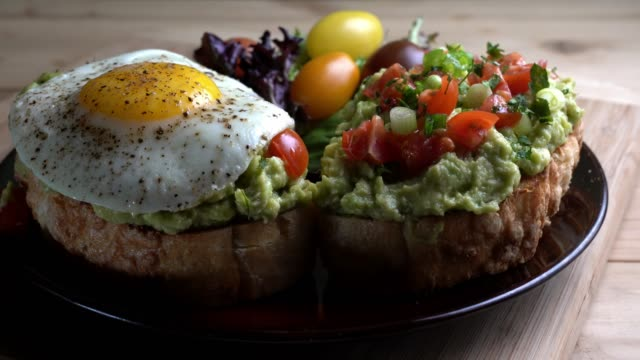 stockvideo's en b-roll-footage met avocado toast gegarneerd met blokjes tomaten, gehakte groene ui besprenkeld met olijfolie en gebakken ei - ei
