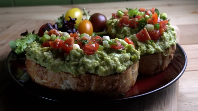 Avocado Toast Topped With Diced Tomatoes Chopped Green Onion Drizzled With Oliv Oil Toasted artisan asiago bread topped with chunky avocado and chopped tomatoes, green onion drizzled with olive oil avocado stock videos & royalty-free footage