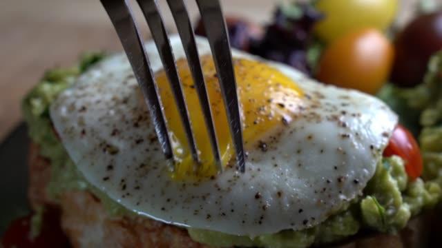 stockvideo's en b-roll-footage met avocado toast gegarneerd met blokjes tomaten groene ui en gebakken ei met een vork de dooier piercing - ontbijt