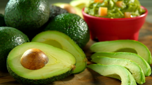 Avocados whole and sliced on a wooden chopping board. Avocados whole and sliced on a wooden chopping board with a bowl of guacamole and tomato. Tight shot. avocado stock videos & royalty-free footage