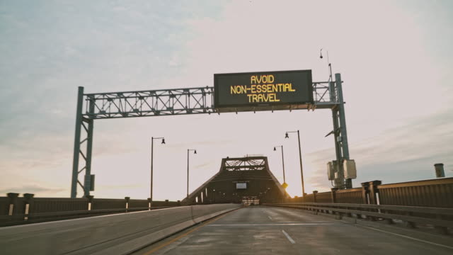"""Avoid non-essential travel"" advisory on a road sign on General Pulaski Skyway Bridge flashing because of COVID-19 Coronavirus pandemic in New Jersey. Driver point of view."