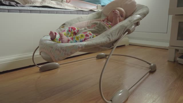 Awake and active baby girl in bouncy seat at home Baby girl of two months resting in bouncy seat in the bedroom. Awake child moving arms and legs rocking chair stock videos & royalty-free footage