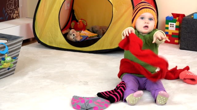 Awesome baby girl measure colorful knitted scarf and hat between toys in room. video