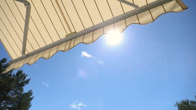 markis öppettider mot blå himmel på solig dag - kanvas bildbanksvideor och videomaterial från bakom kulisserna