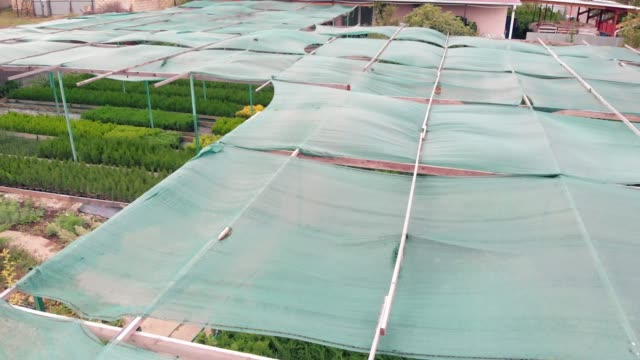 Awning that creates a shadow for cultivated plants and flowers. Aerial view. Canopy over an eco farm
