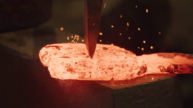 CU of axe cutting glowing red hot ingot by Master Sword smith with sparks flying. Traditional Japanese forge method. Japan Craft Culture. CU of axe cutting glowing red hot ingot by Master Sword smith with sparks flying. Traditional Japanese forge method. Japan Craft Culture. blacksmith shop stock videos & royalty-free footage