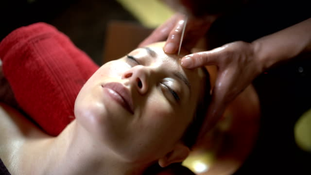 Ayurveda relaxation Ayurveda therapist massaging forehead of a young woman that lies on the massage table; Warm aromatic oil leaking on her forhead massage oil stock videos & royalty-free footage