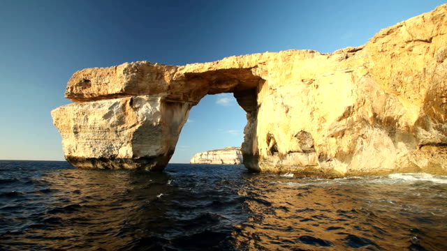 Azure Window, known as Tieqa Żerqa Pan shot view of Azure Window, known as Tieqa Żerqa, a natural rock formation on the coast of Gozo island, Malta malta stock videos & royalty-free footage
