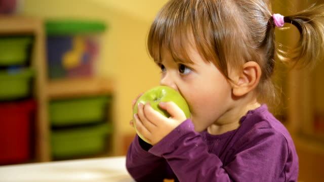 Babies and food, female child eating green apple in kindergarten video