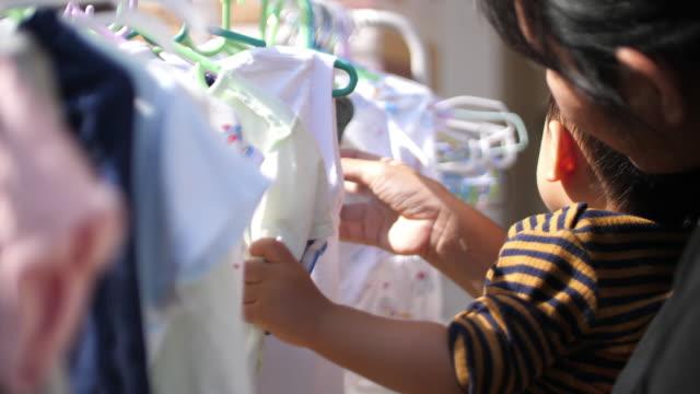 baby and mother choosing cloth - abbigliamento da neonato video stock e b–roll