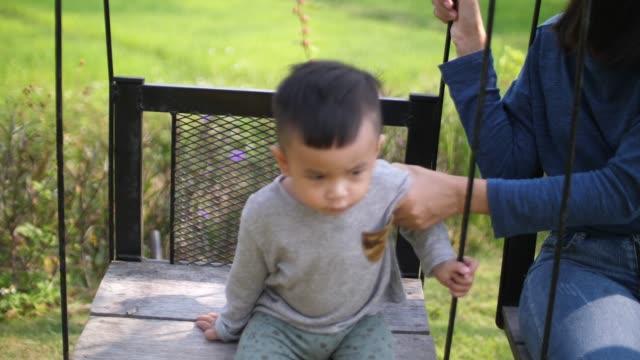 baby und mutter spielen schwung - gold waschen stock-videos und b-roll-filmmaterial