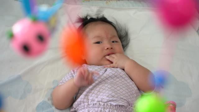 vídeos de stock, filmes e b-roll de menina asiática de bebê no berço, olhando para o brinquedo móvel. - mobile