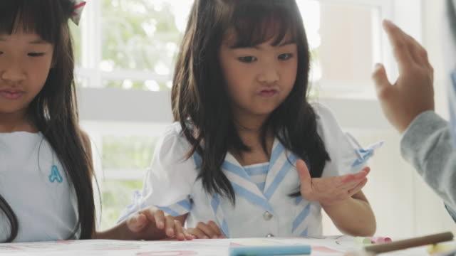 asiatische mädchen auf der zeichnung klassenzimmer - schulmaterialien stock-videos und b-roll-filmmaterial