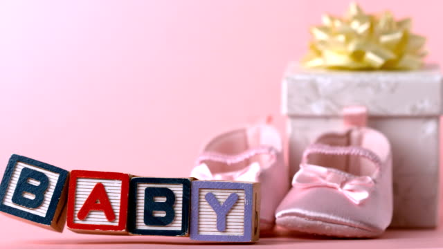 Baby blocks toppling over Baby blocks toppling over in front of booties and gift box in slow motion baby booties stock videos & royalty-free footage