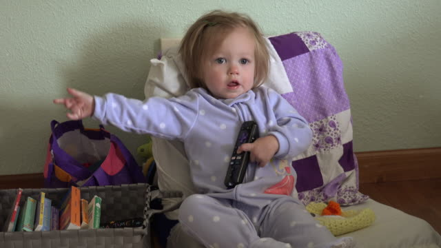 Baby blue pajamas holding tv remote controller seated with books. video