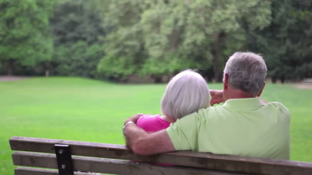 Baby boomer couple on bench kiss. video