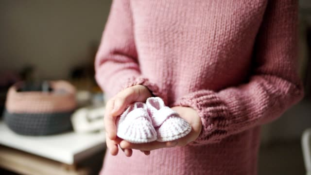 Baby booties on female palms. Knitted shoes handmade for children Baby booties on female palms. Close up knitted booties for newborn baby in mother hands. Knitted shoes handmade for children. Expecting mother in knitting wear baby booties stock videos & royalty-free footage