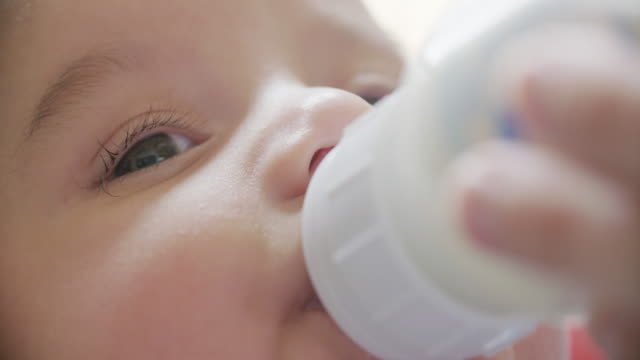 Baby Bottle Feeding Close Up Slow Motion a slow motion close up of a 3 month old baby feeding from a bottle feeding stock videos & royalty-free footage
