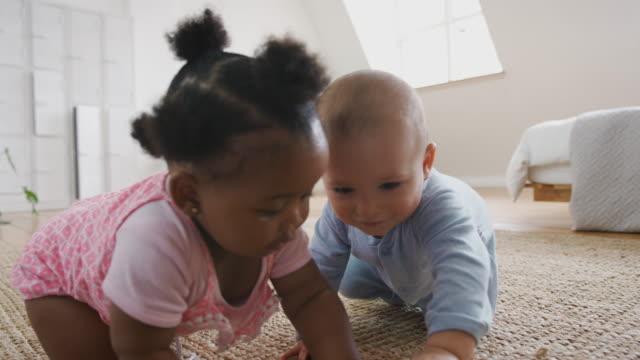 vidéos et rushes de garçon et fille de chéri jouant avec des jouets sur le rug à la maison ensemble - ramper